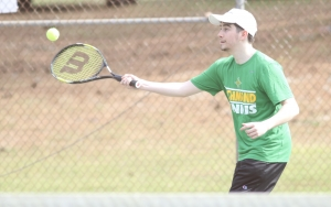 Senior Douglas McDonald returns the ball during his singles match win during the first match of Tuesday's doubleheader.