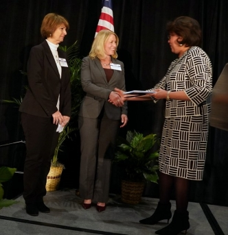 Beth Walker, president of FirstHealth Montgomery Memorial Hospital, and Roxanne Elliott, policy director of FirstHealth Community Health Services, accept the award from Phyllis Wingate, past chair of the NCHA Board of Trustees.