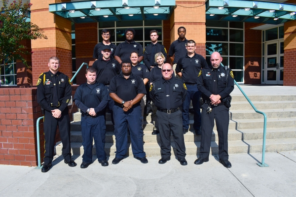 Graduates of Richmond Community College's Detention Officer Certification training program stand with their instructors on the steps of the Cole Auditorium.