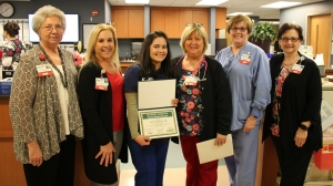 Sara Chaparro, R.N., is presented the January 2019 DAISY Award Winner for FirstHealth of the Carolinas. Sara (center, holding award) is pictured with (from left to right): Debbie Brand, R.N., clinical practice coordinator; Karen Robeano, DNP, R.N., FirstHealth's chief nursing officer; Tammy Stafford, R.N., assistant nurse manager, surgical admissions unit; Scarlett Blue, R.N., administrative director, surgical services; and Deana Kerns, R.N., MSN, administrative director of corporate education and professional development. For more information on the DAISY Award, or to nominate a deserving nurse, visit www.firsthealth.org/daisy.