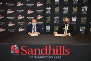 Sandhills CC President Dr. John Dempsey, left, and UNCP Chancellor Robin Gary Cummings sign a BraveStep agreement during a small ceremony at Sandhills Community College on Thursday.