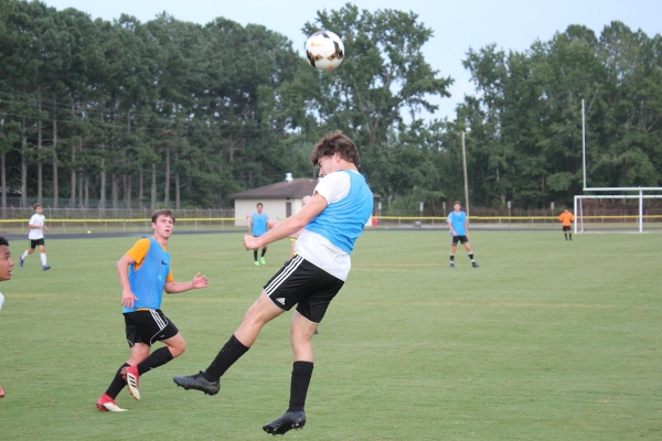 Senior forward Luke Hawks heads the ball during Tuesday's scrimmage against Grays Creek.