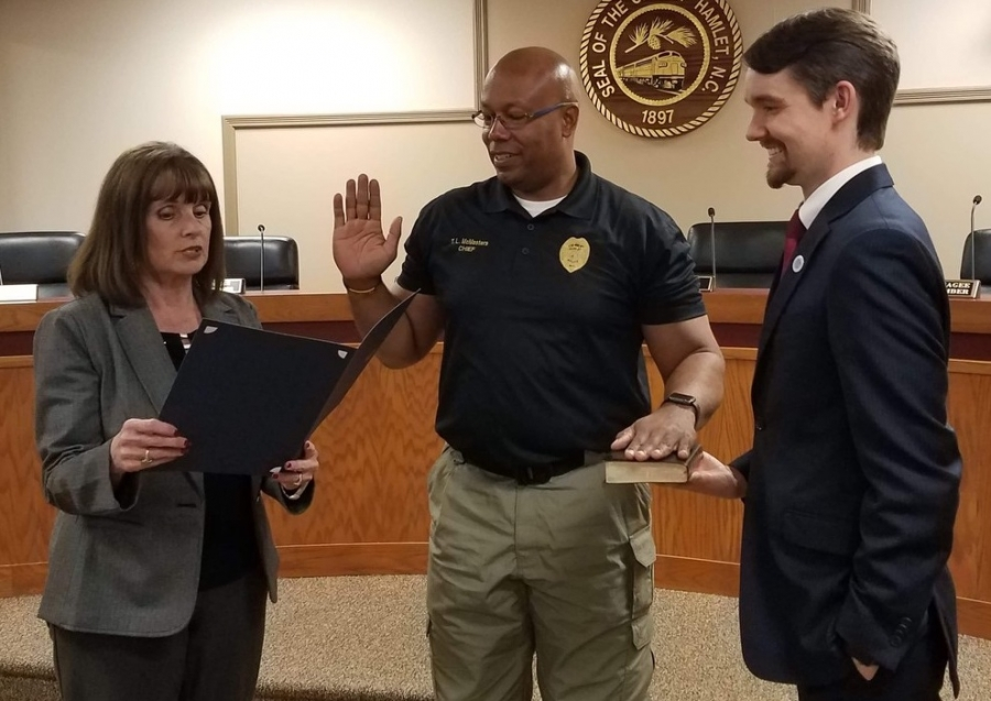 New Hamlet Police Chief Tommy McMasters Jr. is sworn in Tuesday by City Clerk Gail Strickland while City Manager Jonathan Blanton holds the Bible. A formal swearing-in will be next Tuesday.