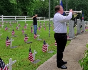 Johnny Patrick of American Legion Post 316 salutes as Cameron McDonald plays Taps during a Memorial Day service at Veterans Memorial Park late Monday morning.