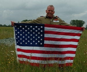 Jon Ring holds a U.S. flag that he jumped with over the tiny village of Angoville au Plain