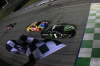 Kurt Busch, driver of the #1 Monster Energy Chevrolet, takes the checkered flag ahead of Kyle Busch, driver of the #18 M&M's Toyota Camry Toyota, to win the Monster Energy NASCAR Cup Series Quaker State 400 Presented by Walmart at Kentucky Speedway on July 13, 2019 in Sparta, Kentucky.