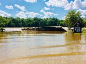 The floating dock at the U.S. 74 boat landing near the bridge rests overturned as a large amount of water from last week's rains made its way downstream.