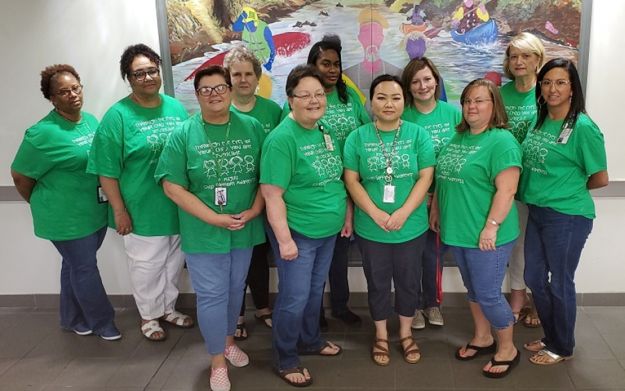 Employees of the Richmond County Child Support office observe Child Support Awareness Month, wearing T-shirts that read: Through the eyes of your child, you are are invincible.