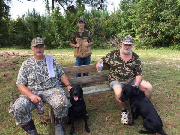 Gary Payne, Elijah Tang, and Kinard Fennell with their dogs, Hope and Ruger.