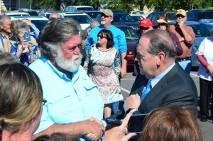 Former Arkansas governor Mike Huckabee, right, meets with T.K. Thrower during a campaign stop Wednesday in Rockingham on behalf of congressional candidate Mark Harris.