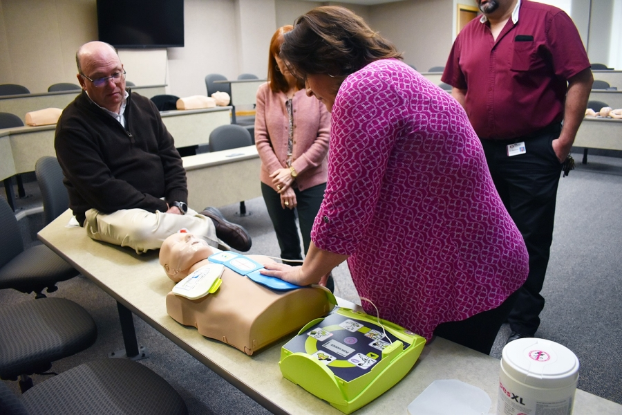 American Heart Association certified instructor Holly Russell shows Dr. Dale McInnis, president of Richmond Community College, and other college employees how to properly use an automated external defibrillators (AED).
